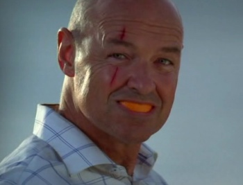 Scary-looking Locke freaking out his fellow LOST-ies with an orange in his mouth